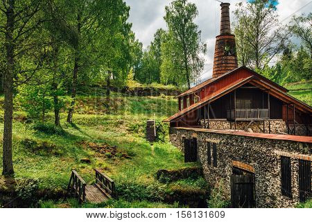 Old red ironworks building. standing in the lush green environment.