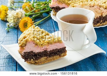 Baking in multicooker. Homemade festive multilayer cake with jam chocolate marshmallows streusel and a cup of tea on a blue wooden background. Selective focus