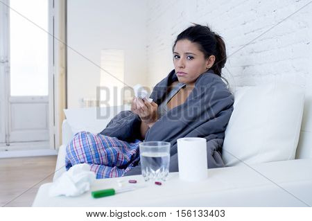 young attractive hispanic woman lying sick at home couch in cold and flu sneezing nose with tissue covering with blanket in gripe disease symptom and health care concept