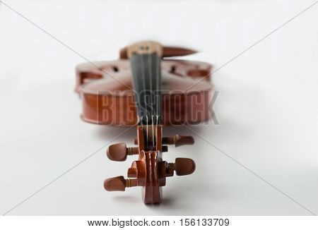horizontal image of a violin lying flat facing up with the tuning pegs closest to the forefront and the body blurring to the background isolated on white background.