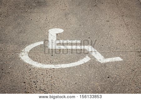 horizontal image of a wheel chair painted onto the pavement marking a spot for handicapped parking with room for text.
