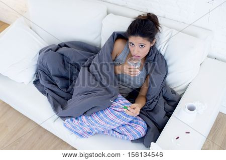 young attractive hispanic woman lying sick at home couch in cold and flu taking temperature with thermometer covered with blanket in gripe disease symptom and health care concept