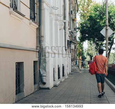 young man is going down on the street, view from back, summer warm day