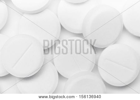 Medical concept or theme image with pills in the foreground. Product photo taken from above, low angle. Top view of medical pills on a white table.