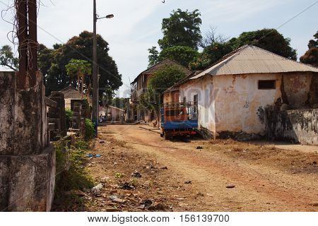 A street in Bolama former capital of the Portuguese colony in the background visible post-colonial buildings