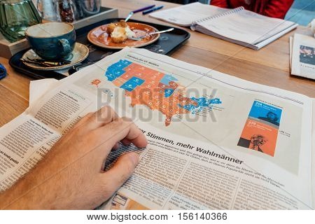 FRANKFURT, GERMANY - NOV 10 2016: US map election results - Man reading Frankfurter Allgemeine Zeitung newspapper with Donald Trump elected as President as the 45th President of United States of America