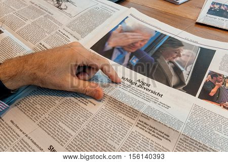 PARIS FRANCE - NOV 10 2016: Pointing to Hillary and Bill Clinton - Man reading Frankfurter Allgemeine Zeitung newspapper with Donald Trump elected as President as the 45th President of United States of America