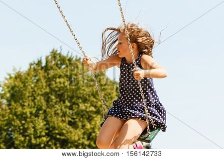 Craziness and freedom. Young summer girl playing on swing-set outdoor. Crazy playful child swinging very high to touch the sky.