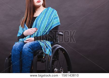 Health disease disability invalid tragedy concept. Girl on wheelchair. Young crippled lady sitting calmly looking around.