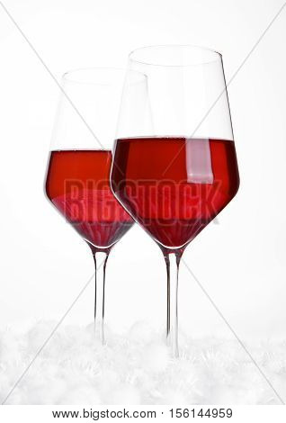 Glasses of red wine on snow balls on white background