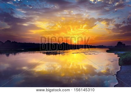 Summer river landscape with multicolored sunrise. Lake landscape. Beautiful landscape with golden sunset.