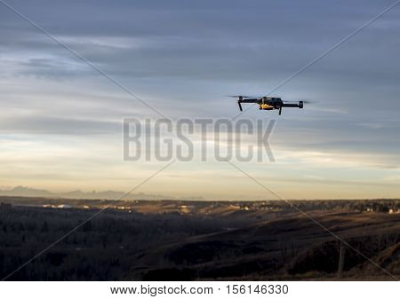 Small modern drone hovering taking picture of mountains at sunset