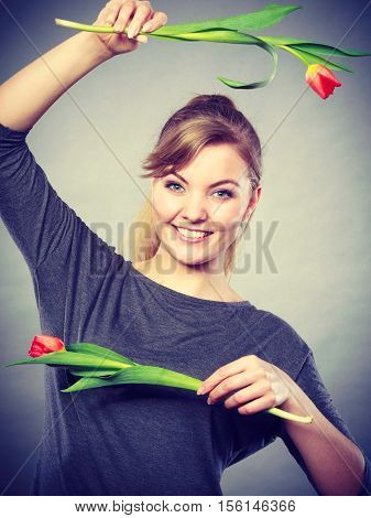 Spring time. Craziness and fun concept. Playful happy girl playing with flowers. Joyful smiling funny positive female person making crazy figures with tulips.