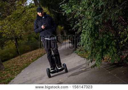 Young man riding electrical scooter with mobile phone - hoverboard in the city park