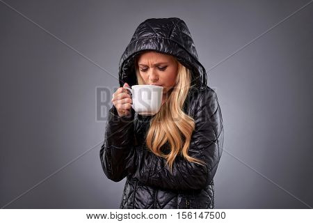 A beautiful young woman standing in a winter jacket drinking from a mug while feeling unwell