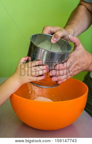 Children and dad hands Sift flour in yellow bowl