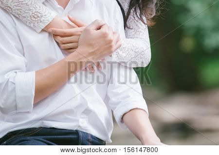 Romantic asian couple hugging on nature background