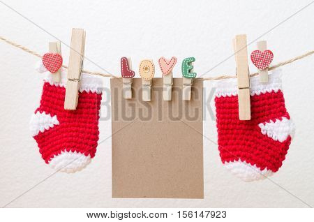 Blank paper with baby socks hanging on love clothesline