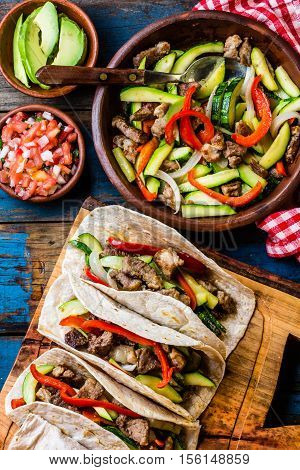 Mexican pork tacos with vegetables and salsa. Tacos al pastor on wooden blue rustic background. Top view