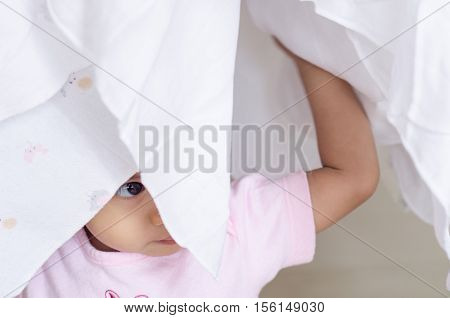 Happy little baby girl hidden her face in white cloth diaper