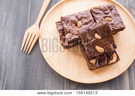 Chocolate brownie with cashew nuts on wooden background.