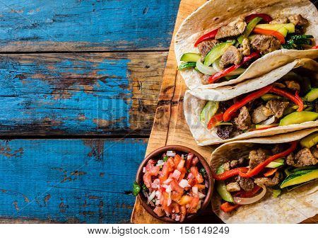 Mexican pork tacos with vegetables and salsa. Tacos al pastor on wooden blue rustic background. Top view. Copy space