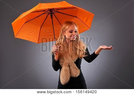 A beautiful young woman screaming while holding an umbrella wearing a stole