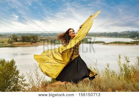 Oriental Beauty dance with wings. Nice girl in national dress dancing in the open air. Nomads. Firebird.