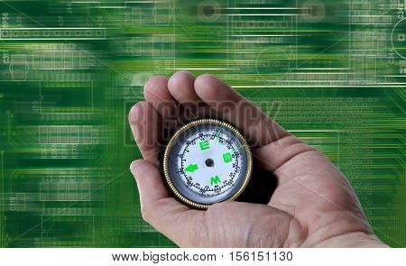 Compass in hand looking with high tech background.