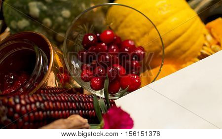 Blank Card in an abundant healthy autumn gift basket with candied cranberry home made compote indian corn and sweet pumpkin slice to say thank you or deliver a special message on blank copy space with the warmth of the season