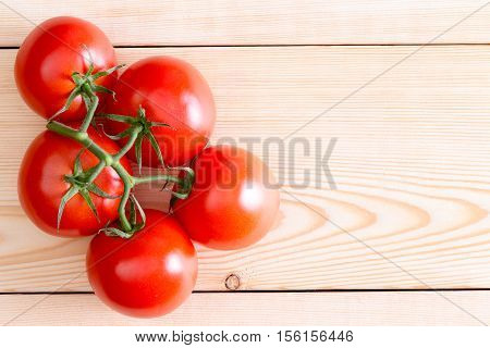 Five Medium Tomatoes Over Unfinished Wooden Planks
