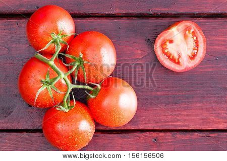 Half Of A Tomato With Cluster Over Dark Table