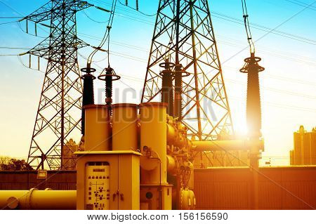 Close-up of high-voltage power substation equipment evening landscape.