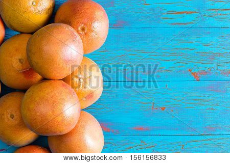 Stacked Whole Grapefruits Over Blue Surface