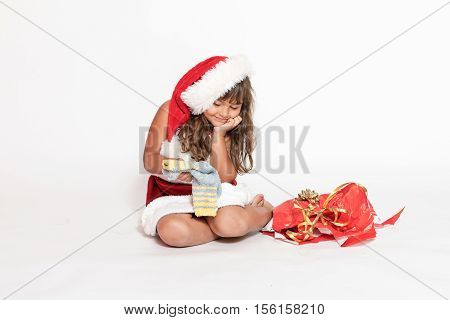 Smiling little girl in Santa Claus costume is looking at an inappropriate gift (socks).