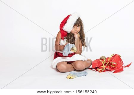 Sad little girl in Santa Claus costume is holding inappropriate gift (socks).