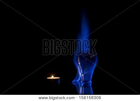 Small candle and tungsten light bulb burning with a beautiful blue flame