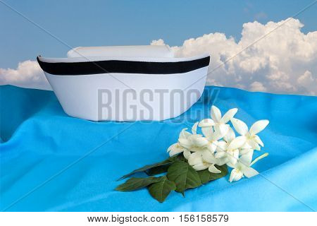 Hat nurse white and Millingtonia hortensis flowers on blue fabric. symbol of nursing thailand and Thai traditional medicine. Object with work paths for cutout background poster