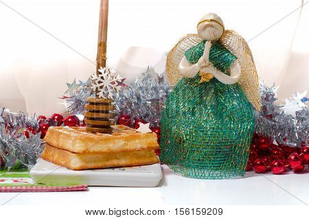 Christmas Angel with praying hands say thank you for tasty Waffel with honey