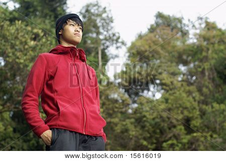 Asian standing outdoors looking far away