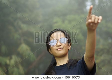 Confident asian teen girl pointing