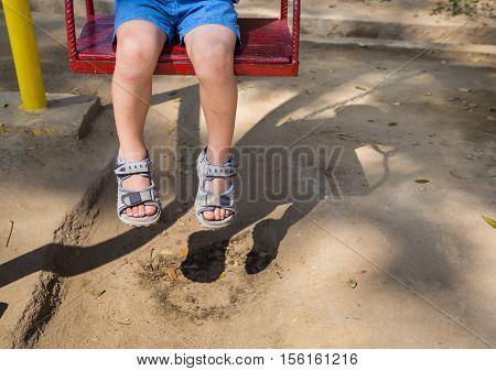 Foot baby swinging on swing at playground