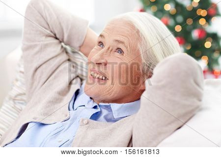 age, holidays, relax and people concept - happy smiling senior woman resting on sofa and dreaming at home over christmas tree background