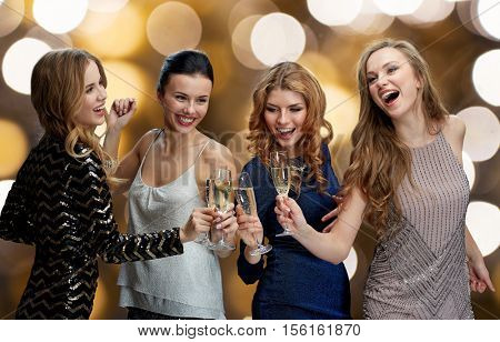 celebration, friends, bachelorette party and holidays concept - happy women clinking champagne glasses and dancing over lights background