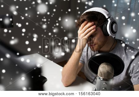 technology, gaming, entertainment, let's play and people concept - close up of sad young man in headset with pc computer streaming playthrough or walkthrough video game and loosing at home over snow