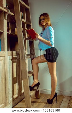 young woman librarian in the glasses read a book next to the bookshelf