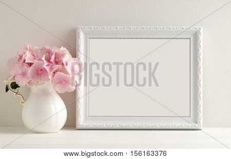 White landscape frame mockup with a vase of hydrangea beside the frame overlay your quote promotion headline or design great for small businesses lifestyle bloggers and social media campaigns