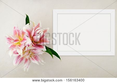 White landscape flat lay frame mockup with rose lillies beside the frame overlay your quote promotion headline or design great for small businesses lifestyle bloggers and social media campaigns