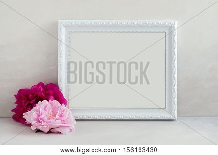White landscape frame mockup with a 2 pink peonies beside the frame overlay your quote promotion headline or design great for small businesses lifestyle bloggers and social media campaigns