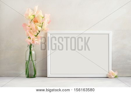 White frame mockup with a vase of sweet peas beside the frame overlay your quote promotion headline or design great for small businesses lifestyle bloggers and social media campaigns